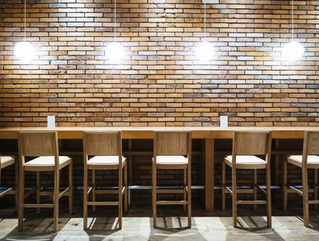 Foto de Table counter Bar with Chairs and Lights Brick wall background Hipster Loft Interior - Imagen libre de derechos