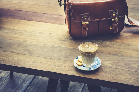 Foto de Coffee on wooden table with leather Bag Hipster lifestyle outdoor - Imagen libre de derechos