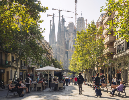 Foto de SPAIN, BARCELONA - OCT 21, 2018 : Cafe restaurant Cozy street in Barcelona city People walking Sagrada Familia Architecture landmark - Imagen libre de derechos