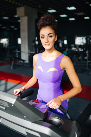 Foto per Sport world. Woman in violet sportswear running on a treadmill in front of window at gym. Jogging her way to good health. - Immagine Royalty Free