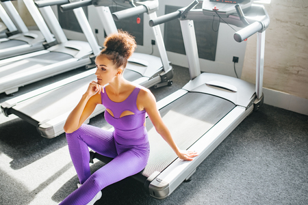 Foto per Sport young fitness girl in sport wear relaxing on the treadmill in the gym, Exercise working out with copy space. Runnig machine - Immagine Royalty Free