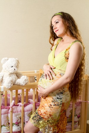 Pregnant woman with long hair with toy Teddy bear in a crib at home. The concept of the family and parents