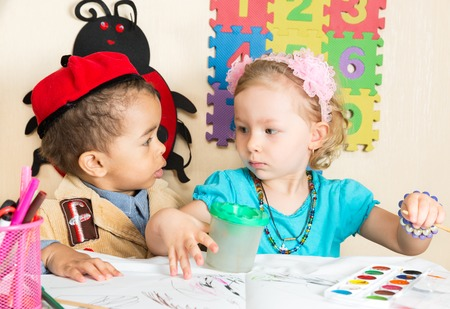 African American black boy and girl drawing with colorful pencils in preschool at table in kindergarten