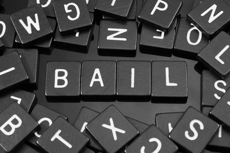 Foto de Black letter tiles spelling the word bail on a reflective background - Imagen libre de derechos