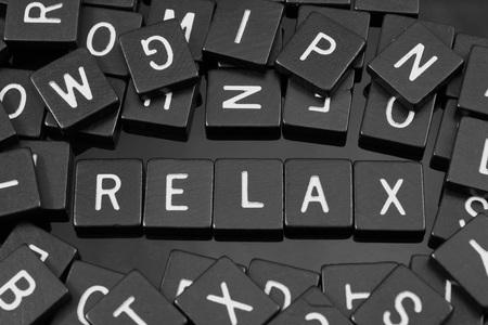 Photo pour Black letter tiles spelling the word relax on a reflective background - image libre de droit