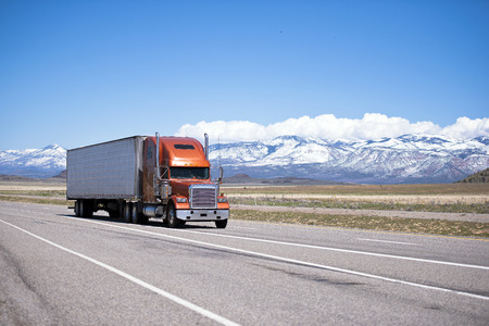 Large orange modern classic beautiful well maintained semi truck with two straight pipes and white refrigerator trailer on a highway against the backdrop of snow-capped mountain ranges and clear blue sky