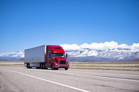 Photo for Large beautiful modern classic-modern red truck with a high cab and trailer on a flat stretch of highway on a background of snow-capped mountain ranges, drowning in the clouds and clear blue sky - Royalty Free Image