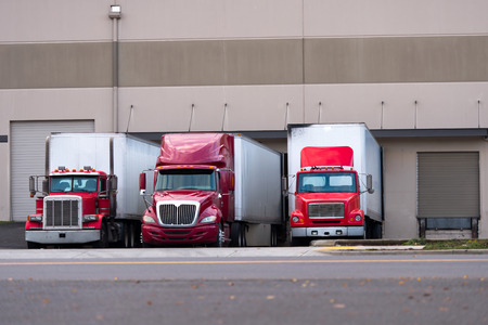 Photo pour Three red semi truck manufacturers and various modifications from the classic old models to modern aerodynamic semi trucks with dry van trailers are standing side by side in one line under the docks warehouse for loading or unloading. - image libre de droit