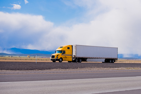 Photo for Classic modern semi truck bright yellow color with a white full length trailer aerodynamic skirts on a flat highway in Utah with the blue mountains on the horizon. Modern tool in the trucking industry. - Royalty Free Image