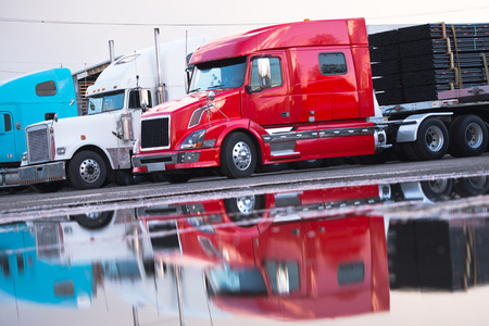 Photo pour Several big rig semi trucks of different models and colors of modern and classic red and white with a trailer in the parking lot with a load in anticipation of unloading reflected in the water on the pavement after the rain. - image libre de droit