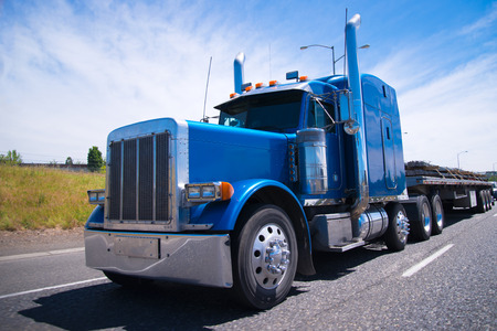 Photo pour Classic blue bonneted big rig semi truck with chrome accessories  - image libre de droit