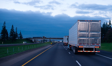 Photo pour The convoy of semi trucks with reefer trailers on flat like an arrow evening road  - image libre de droit