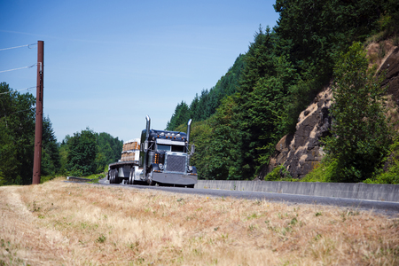 Photo for Powerful spectacular professional commercial classic dark blue semi - truck with an open trailer flat bed and chrome accents transports building boards on the highway near the picturesque cliffs covered with green trees. - Royalty Free Image