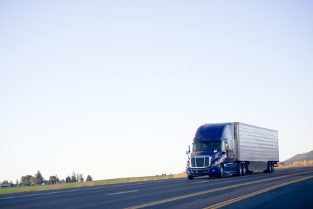 Photo pour Modern huge powerful drivers popular dark blue big rig semi-truck with a sleeping compartment and a periphery on a flat plane of the Highway road on silhouette against the sky monochrome. - image libre de droit