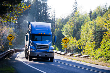 Photo for Large American professional powerful big rig semi truck with a flat bed trailer, transports goods on the winding road through the mountains, surrounded by yellowing autumn trees illuminated by bright sunshine, with road signs on both sides of the road. - Royalty Free Image