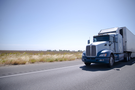 Photo pour Big powerful custom built big rig semi truck with refrigerated trailer transports perishable goods that require storage at low temperature, on straight road in California - image libre de droit
