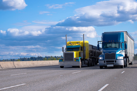 Photo for Two semi trucks of various models and manufacturers, a yellow classic American semi truck with a bulk trailer and a blue modern American semi truck with a high trailer for bulk cargo rushing along a wide highway next to each other - Royalty Free Image