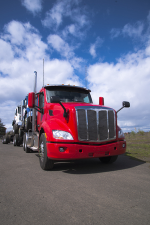Foto de A powerful modern big rig red semi truck carries other articulated lorry semi trucks of various models and colors, loaded one on top of another against a fantastic cloudy sky - Imagen libre de derechos