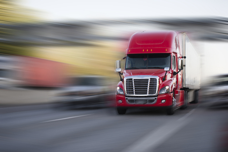 Foto per Bright reach professional comfort red modern big rig semi truck with semi trailer move with cargo on the highway on blurred background - Immagine Royalty Free