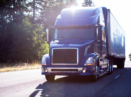 Photo for Popular model of modern dark blue big rig semi truck with dry van trailer transport cargo on the road with trees in sun ray light - Royalty Free Image