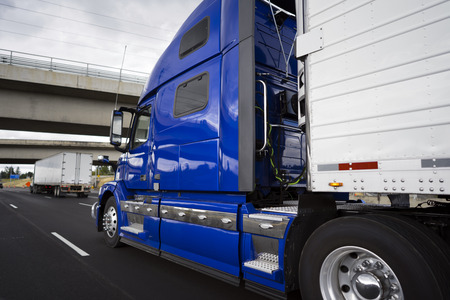 Photo pour Big rig modern bright blue long haul semi truck with refrigerator semi trailer transporting perishable and frozen foods on the wide highway road with crossing bridge and another semi truck - image libre de droit