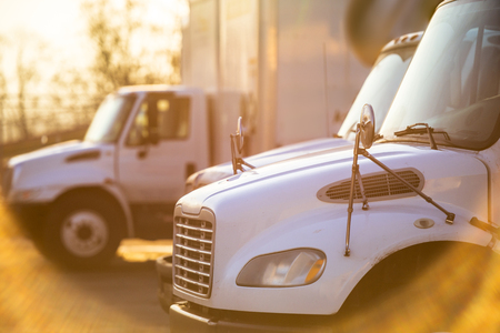 Foto per Middle duty rigs semi Trucks with box trailers standing at the gates of the warehouse for loading commercial cargo for the next local deliveries flooded with sunlight - Immagine Royalty Free