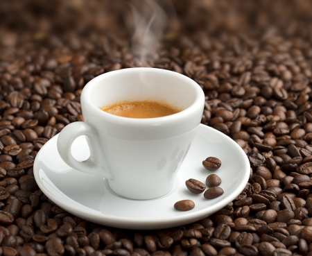 Foto de steaming cup of coffee on background of coffee beans - Imagen libre de derechos