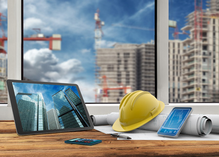 Photo pour tablet, smartphone, safety helmet and blueprints in construction site - image libre de droit