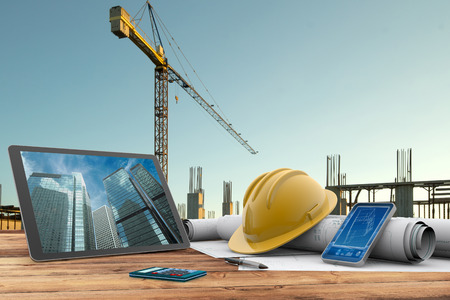 Foto per blueprints, safety helmet and computer in construction site - Immagine Royalty Free