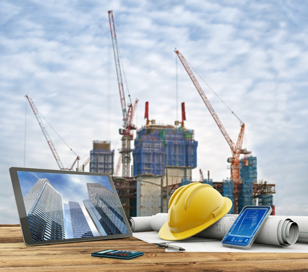 Foto de blueprints and safety helmet over a table in construction site - Imagen libre de derechos