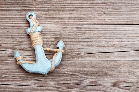 Photo pour small blue anchor on a wooden background - image libre de droit