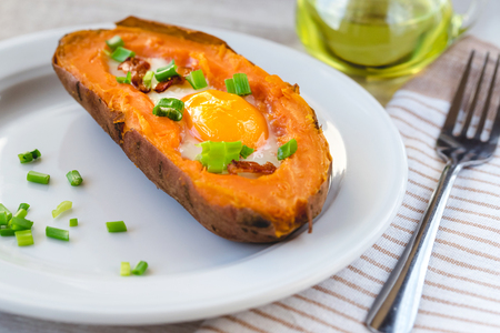Photo for Baked sweet potato with fried egg, bacon and chives. - Royalty Free Image