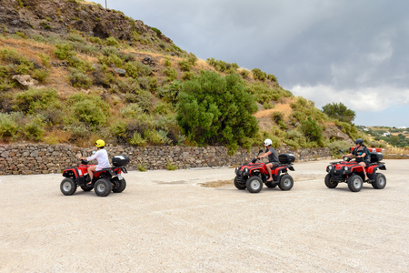 Photo pour Milos, Greece, May 18, 2017: Young people driving quads on road. Quad is very popular means of transport on Milos island. Greece. - image libre de droit