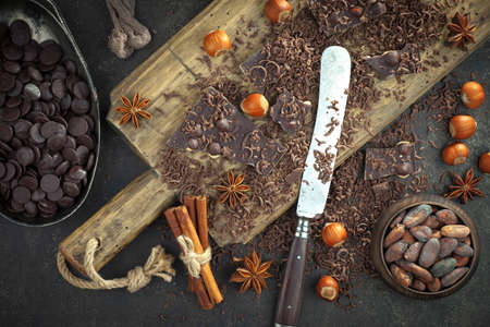 Dark chocolate in a composition with cocoa beans and nuts, on an old background.