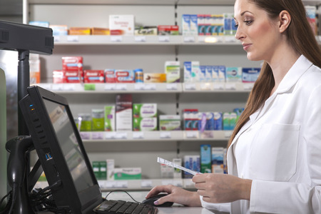 Foto de Female pharmacist searches medicine holding a prescription in her hand - Imagen libre de derechos