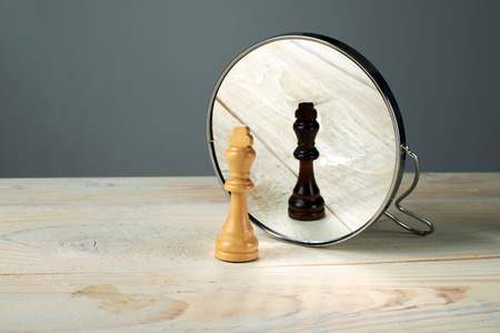 Photo pour Black or white king chessmen in front of the mirror, concept about racism. - image libre de droit