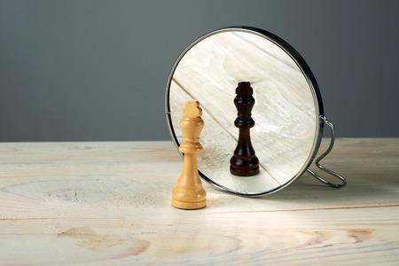 Foto de Black or white king chessmen in front of the mirror, concept about racism. - Imagen libre de derechos