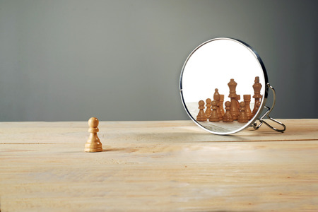 Photo pour You are not alone. Chessmen in front of the mirror - image libre de droit