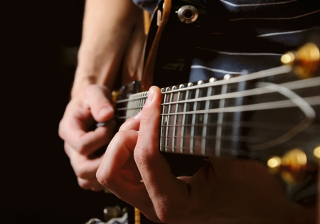 Photo for close up shot of strings and guitarist hands playing guitar over black - shallow DOF with focus on hands - Royalty Free Image