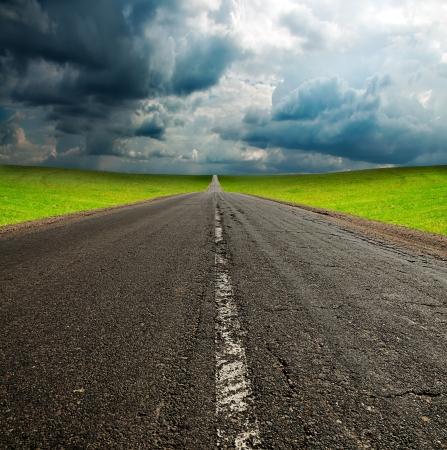 old broken asphault road in green field over blue cloudy sky