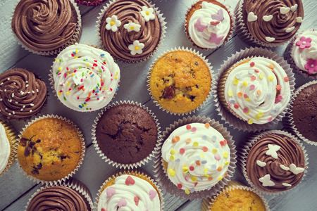 Photo for Multiple colorful nicely decorated muffins on a wooden background, top view - Royalty Free Image