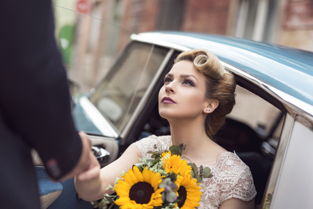 Photo for Beautiful young bride sitting in a wedding dress in a retro old car, holding a sunflower bouquet while groom is helping her get out of the car - Royalty Free Image