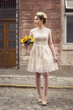 Photo for Beautiful young bride posing in a wedding dress in a retro cobble street, holding a sunflower bouquet - Royalty Free Image