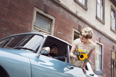 Photo for Young newlywed couple in a retro vintage car, groom driving while bride is waving through a window while they are leaving on their honeymoon. Focus on the bride - Royalty Free Image