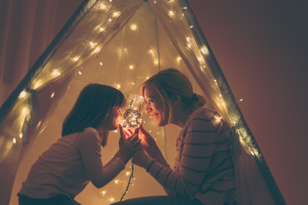 Photo for Mother and daughter sitting in a tent, holding a jar with christmas lights and telling stories. Focus on the mother - Royalty Free Image