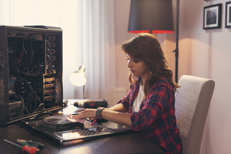 Photo pour Young woman performing a computer maintenance, clearing the dust out of the components - image libre de droit