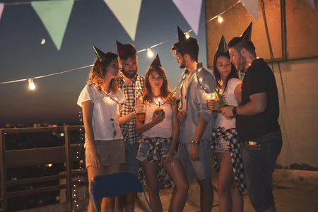 Foto de Group of young friends having a birthday party at a building rooftop, all bored and serious. - Imagen libre de derechos