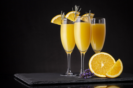 Foto de Mimosa cocktails in champagne glasses with orange juice and sparkling wine decorated with lavender leaves and orange slices - Imagen libre de derechos