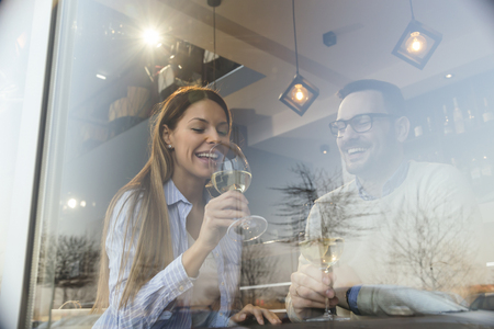 Foto de Portrait of a young couple in love on a date,  sitting at a restaurant table, drinking wine - Imagen libre de derechos