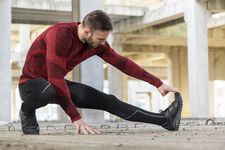 Photo for Athletic, muscular man stretching out and warming up for a workout - Royalty Free Image